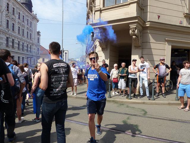Účastník průvodu nese barevnou dýmovnici. Foto: Veronika Charvátová